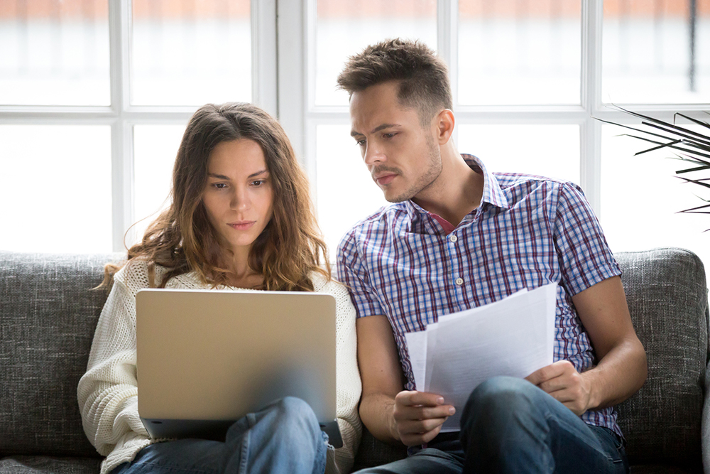 Focused couple researching on computer